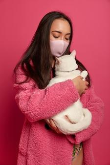 隔離された猫を保持している保護マスクを持つ若い美しい女性の肖像画をクローズアップ