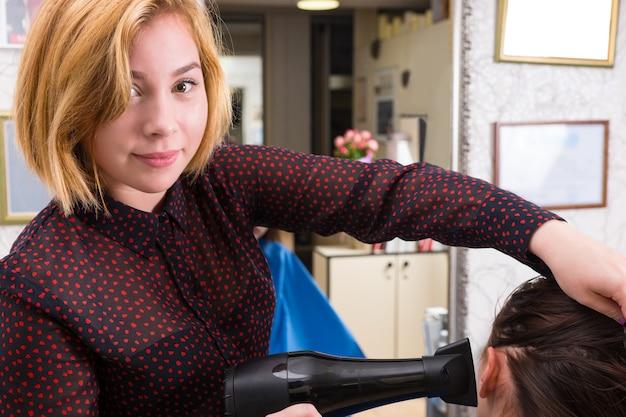 バックグラウンドで大きな鏡とサロンでブロードライヤーとブルネットの女性の髪を乾かしている若いブロンドの女性スタイリストの肖像画をクローズアップ
