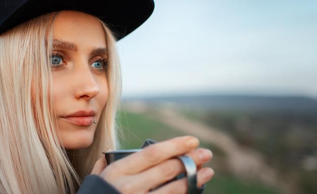 야외 배경 흐리게에 강철 컵을 들고 젊은 금발여 아의 클로즈업 초상화.