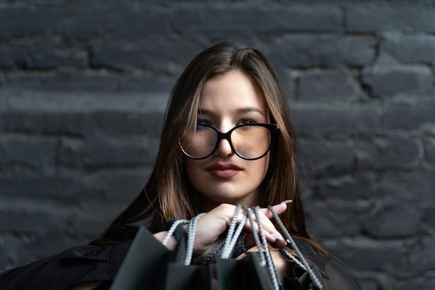 Закройте вверх по портрету молодой женщины брюнетки в очках на фоне черной кирпичной стены.
