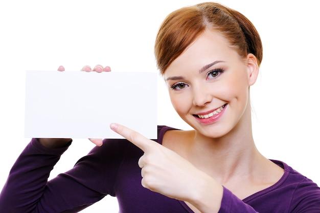 빈 흰색 카드에 가리키는 젊은 백인 웃는 여자의 클로즈업 초상화