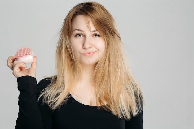 乱雑なブロンドの髪と混乱している若い女性の肖像画を間近します。