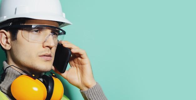 Крупным планом портрет молодой конструкции носить оборудование для обеспечения безопасности и говорить на смартфоне.