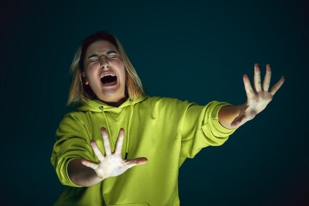 Закройте вверх по портрету молодой сумасшедшей испуганной и потрясенной кавказской женщины, изолированной на темном фоне.