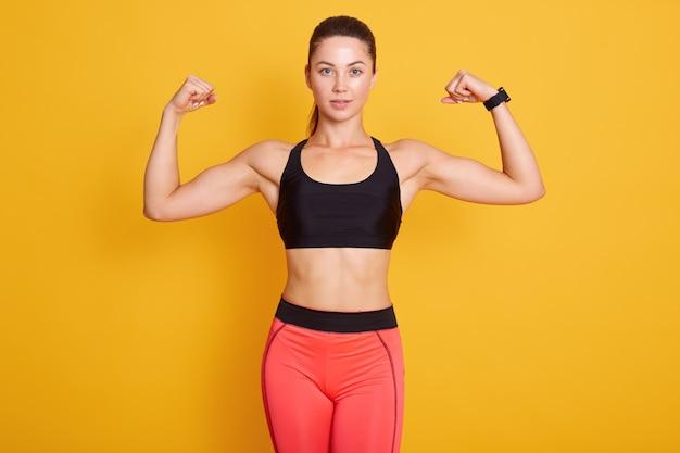 彼女の腕と上腕二頭筋をカメラに見せて、ポニーテールの若いかわいいスポーティなブルネットの女性の肖像画を間近します。女性は黒いブラジャーとレギンスを着ています。スポーツ、健康的なライフスタイル、女性の健康、フィットネスの概念