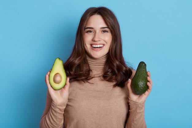緑の新鮮なアボカドの半分が青い壁の上に孤立してポーズをとっている若い黒髪の女性の肖像画をクローズアップ、黒髪の笑顔の女性は有機食品を好む。
