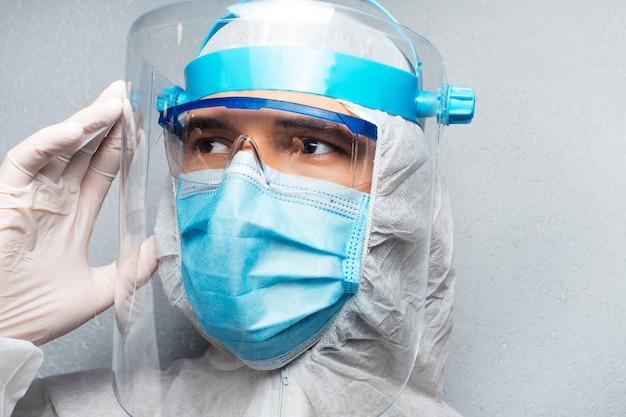 灰色の壁の壁に、コロナウイルスとcovid-19に対してppeスーツを着て、目をそらしている若い医者の男性のクローズアップの肖像画。パンデミックの概念。