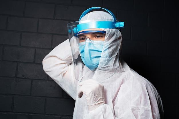 コロナウイルスとcovid-19に対してppeスーツを着た若い医者の男性の接写
