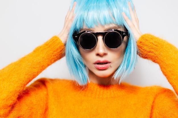 흰 벽에 젊은 유행 자신감 여자의 클로즈업 초상화. 라운드 선글라스와 주황색 스웨터를 입고 파란 머리를 가진 여자.