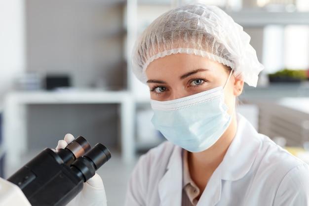 フェイスマスクを着用し、医療研究所で顕微鏡を操作しながらカメラを見ている若い女性科学者の肖像画をクローズアップ、上のスペースをコピー
