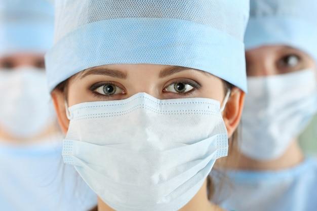 彼女のチームに囲まれた若い女性外科医の医師のクローズアップの肖像画。手術室の外科医のグループ。ヘルスケア、医学教育、救急医療サービスおよび手術の概念