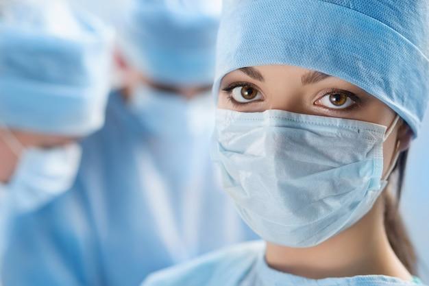Крупным планом портрет молодой женщины-врача-хирурга в окружении ее команды