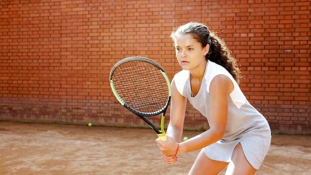 집중하고 그녀의 게임에 집중하는 젊은 여성 테니스 선수의 초상화를 닫습니다