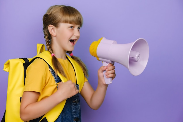 노란색 배낭을 메고 확성기로 비명을 지르며 보라색 배경 벽 어린이 스튜디오에서 고립된 포즈를 취하고 있는 재미있는 금발 여학생의 초상화를 닫습니다. 교육 라이프 스타일 개념