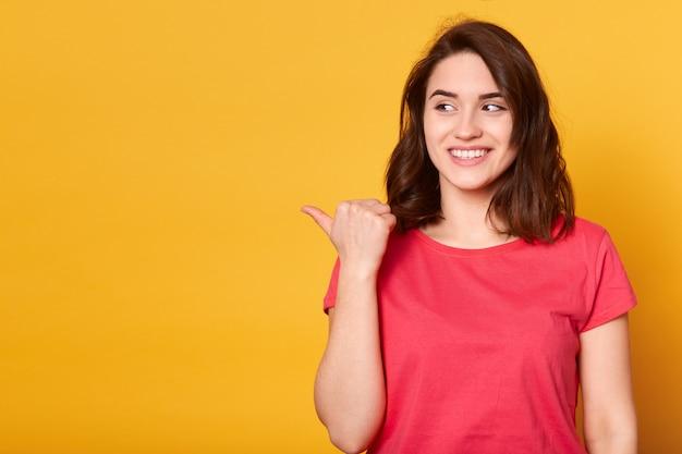 親指で左を指し、幸せな表情と歯を見せる笑顔でよそ見カジュアルな服装の若い格好のギャーク髪の女性の肖像画を間近します。