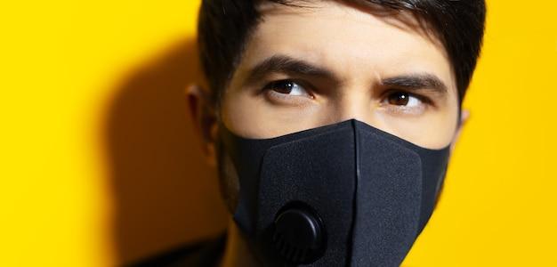 黄色の背景にコロナウイルスに対して黒い呼吸フェイスマスクを身に着けている若い男のクローズアップの肖像画。