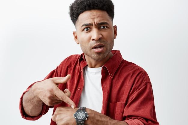 Закройте вверх по портрету молодого красивого чернокожего человека с афро прической в вскользь белой футболке под красной рубашкой указывая на под рукой часы с неудовлетворенным выражением, после того как его друг опоздал.