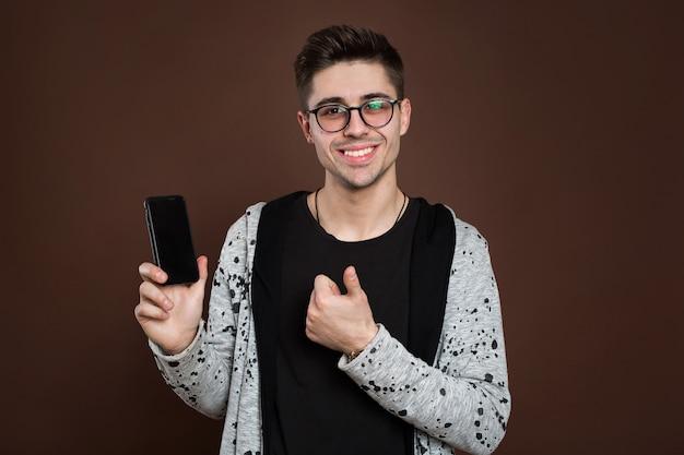갈색 배경 위에 절연 카메라에 스마트 폰 보여주는 젊은 잘 생긴 남성 모델의 초상화를 닫습니다.
