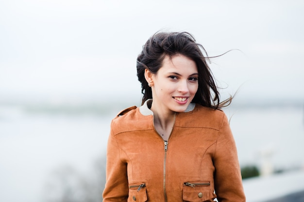 笑顔と明るい屋外の背景の上に立って革のコートを着ている若い幸せな美しい魅力的な女性のクローズアップの肖像画。風が彼女の髪を吹きます。