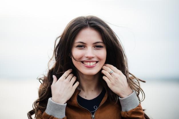 笑顔と明るい屋外の背景の上に立って革のコートを着ている若い幸せな美しい魅力的な女性のクローズアップの肖像画。