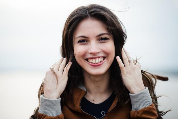 笑顔と立っている革のコートを着ている若い幸せな美しい魅力的な女性のクローズアップの肖像画