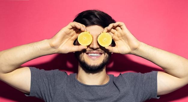 目にレモンを保持している若い幸せな男のクローズアップの肖像画