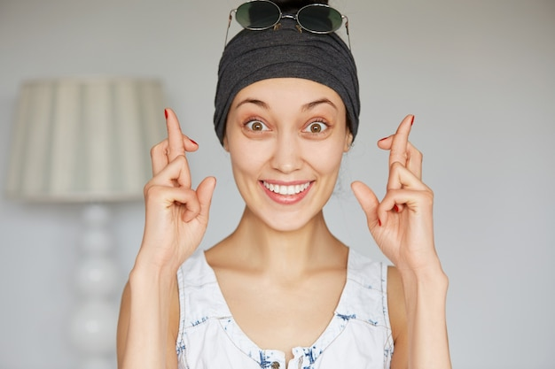 彼女の指を交差する若い幸せな迷信的な女性の肖像画を閉じる