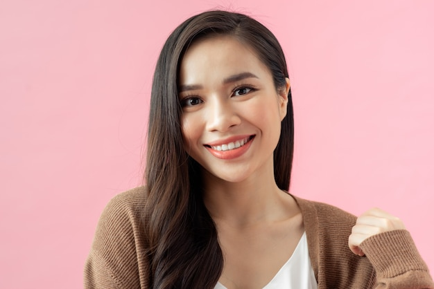 Крупным планом портрет молодой счастливой женщины на розовом фоне