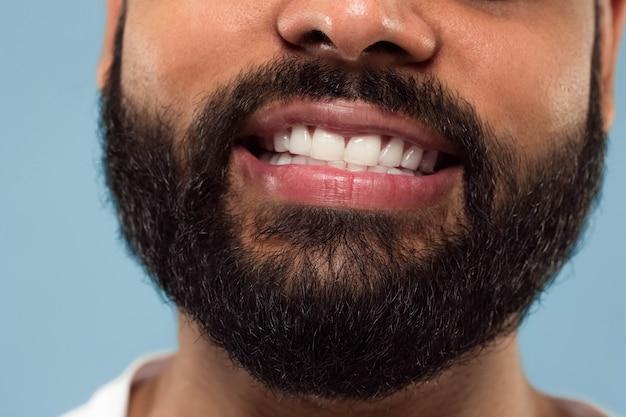 수염, 하얀 치아와 입술 파란색 배경에 젊은 힌두교 남자의 얼굴의 초상화를 닫습니다. 웃고. 인간의 감정, 표정, 광고 개념. 부정적인 공간.