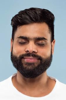 파란색 배경에 고립 된 흰 셔츠에 수염을 가진 젊은 힌두교 남자의 초상화를 닫습니다. 인간의 감정, 표정, 광고 개념. 부정적인 공간. 눈을 감고 꿈꾸는 것.