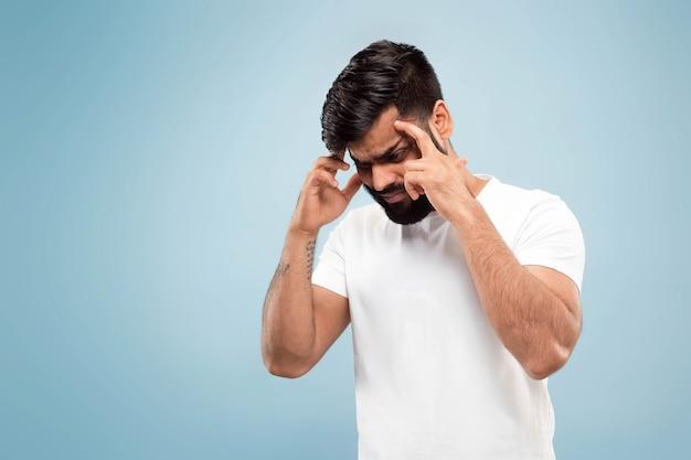 白いシャツを着た若いインド人の肖像画をクローズアップ。集中し、頭痛に苦しんでいます。
