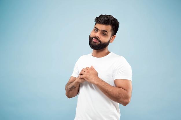 白いシャツを着た若いインド人の肖像画をクローズアップ。ポーズをとって、立って、笑って、落ち着いて見えます。