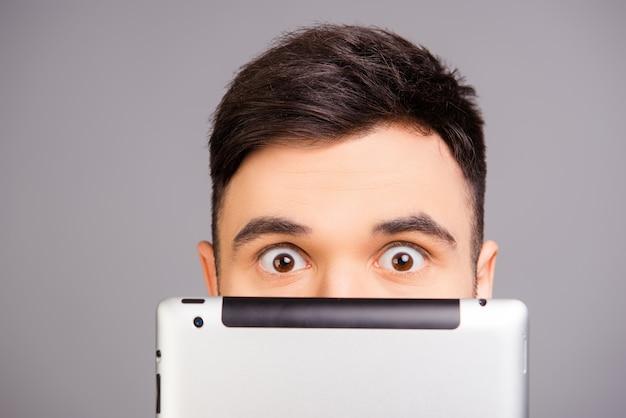 Крупным планом портрет молодого человека, пряча лицо за планшетом
