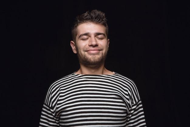 孤立した若い男の肖像画をクローズアップ。目を閉じた男性モデル。考えて笑う。顔の表情、人間の感情の概念。
