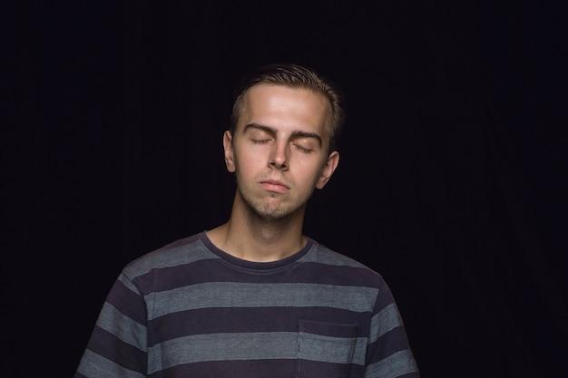 孤立した若い男の肖像画をクローズアップ。目を閉じた男性モデル。思いやりがある。顔の表情、人間性、感情の概念。
