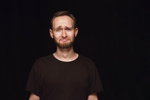 검은 공간에 고립 된 젊은 남자의 초상화를 닫습니다. 남성 모델의 실제 감정이 담긴 포토 샷. 울고, 슬프고, 지루하고 절망적
