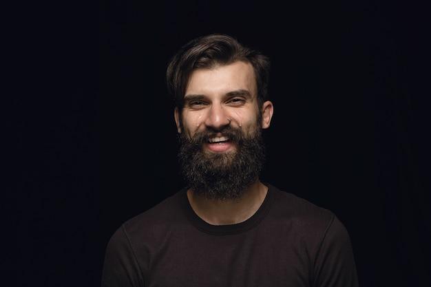 검은 스튜디오 배경에 고립 된 젊은 남자의 초상화를 닫습니다. 남성 모델의 실제 감정이 담긴 포토 샷. 웃고 웃으며 울고 있습니다. 표정, 인간의 감정 개념.