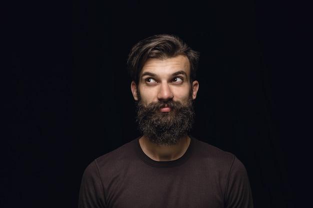 검은 스튜디오 배경에 고립 된 젊은 남자의 초상화를 닫습니다. 남성 모델의 실제 감정이 담긴 포토 샷. 꿈꾸고 웃고, 희망적이고 행복합니다. 표정, 인간의 감정 개념.
