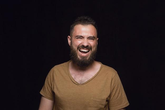 검은 스튜디오 배경에 고립 된 젊은 남자의 초상화를 닫습니다. 남성 모델의 실제 감정이 담긴 포토 샷. 웃고, 미친 행복 함을 느끼고, 웃음. 표정, 인간의 감정 개념.