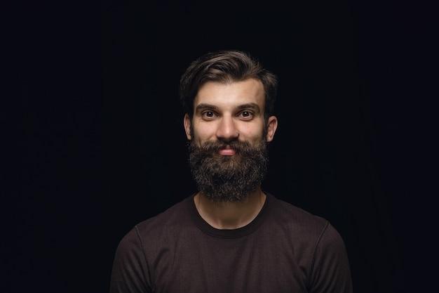 黒のスタジオの背景に分離された若い男の肖像画を閉じます。男性モデルの本当の感情の写真撮影。笑顔、幸せな気持ち。顔の表情、純粋で明確な人間の感情の概念。