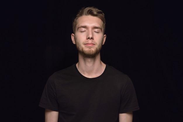 黒のスタジオの背景に分離された若い男の肖像画を閉じます。目を閉じた男性モデルの本当の感情の写真撮影。思いやりがある。顔の表情、人間性、感情の概念。