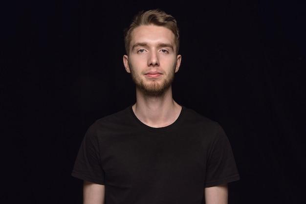 검은 스튜디오 배경에 고립 된 젊은 남자의 초상화를 닫습니다