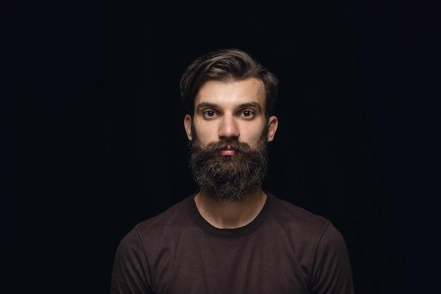 黒のスタジオの背景に分離された若い男の肖像画をクローズアップ