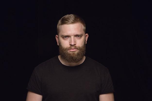 Крупным планом портрет молодого человека, изолированного на черной студии