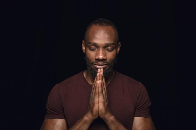 黒い壁に孤立した若い男の肖像画を閉じます。男性モデルの本当の感情の写真撮影。目を閉じて祈って、希望に満ちているように見えます。顔の表情、人間の感情の概念。