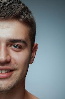 灰色の背景に分離された若い男のクローズアップの肖像画。白人男性モデルが直接見て、ポーズをとって、笑っています。
