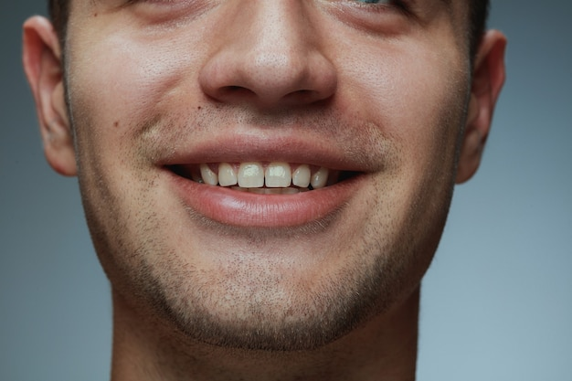 Крупным планом портрет молодого человека, изолированные на сером фоне. лицо и губы кавказской мужской модели.