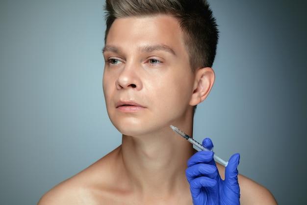 회색 배경에 고립 된 젊은 남자의 클로즈업 초상화. 충전 수술 절차, 입술 및 광대뼈.