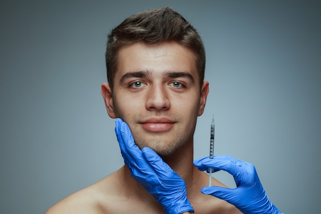 회색 배경에 고립 된 젊은 남자의 클로즈업 초상화. 충전 수술 절차.