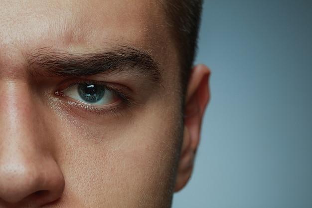 회색 스튜디오 배경에 고립 된 젊은 남자의 클로즈업 초상화. 백인 남성 모델의 얼굴과 파란 눈. 남성의 건강과 미용, 자기 관리, 신체 및 피부 관리, 의학 또는 생리학의 개념.